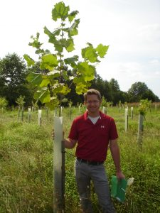 Loudoun SWCD Urban Ag/Conservationist Chris Van Slack with a sycamore tree planted a year-and-a-half earlier in a riparian forest buffer zone in Ashburn.